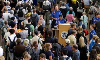 In this photo taken Tuesday, Aug. 11, 2015, at Seattle-Tacoma International Airport, TSA agents are surrounded by travelers in lines that snake past, in Seattle. When it comes to counting passengers, Sea-Tac is the fastest growing of the top 20 airports in the United States, which is putting a strain on services and creating long lines at the security check points. A record 4 million passengers passed through the airport in June. When the numbers are counted for July, they'll likely top June's record and August is always a busy month of the year. (AP Photo/Elaine Thompson)