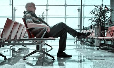 Senior white man relaxing  in a chair in the Dubai airport waiting area. The man is dressed in a striped polo, black trousers and black shoes. (Photo: iStock)